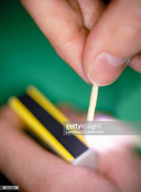 Fingers holding a match as it ignites
