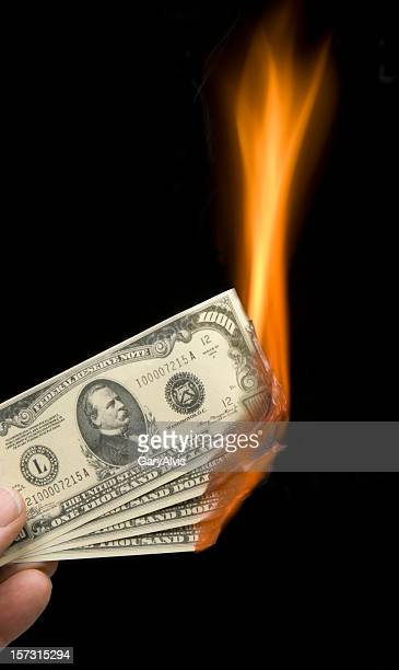 Fingers holding burning thousand dollar bills-money to burn