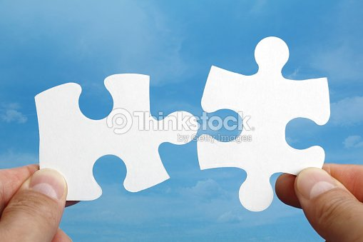 Fingers holding two pieces of a puzzle that fit together : Stock Photo