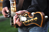 A closeup on a man's left hand playing a Banjo. The Banjo is out of focus except for the neck where his hands are playing a chord. The Banjo hangs from a leather strap around his body. His head is not