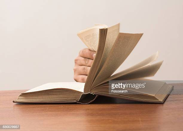 Fingers turning pages in a book