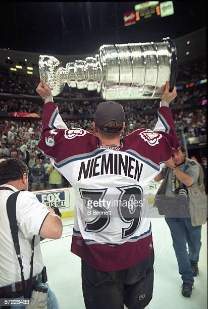 Finishborn professional hockey player Ville Nieminen left wing for the Colorado Avalanche stands on the ice and hoists the Stanley Cup above his head...