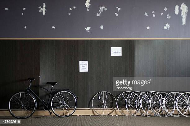A finished bicycle and hand made wheels lean against a wall at the Detroit Bike manufacturing facility in Detroit Michigan US on Thursday June 25...