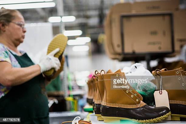 Finished boots sit on a conveyor belt before being packaged at the LL Bean Inc manufacturing facility in Brunswick Maine US on Wednesday Sept 9 2015...