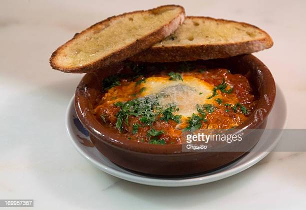 Finished dish of egg poached in tomato sauce in wood burning oven Patria Executive Chef Stuart Cameron shows Corey Mintz how they make 2 dishes from...