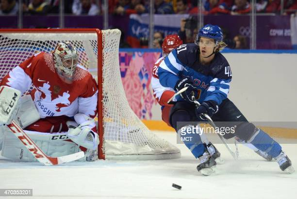 Finland forward Antti Pihlstrom passes from around the Russia goal against Russia defenseman Slava Voynov and Russia goalie Semyon Varlamov in the...