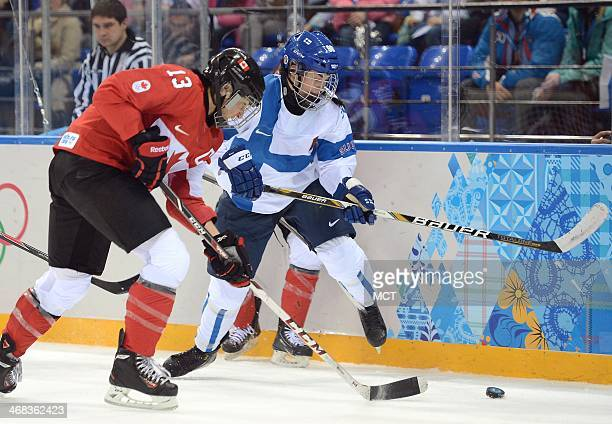 Finland forward Emma Nuutinen and Canada forward Caroline Ouellette go after the puck in the second period of a Winter Olympics women's hockey game...