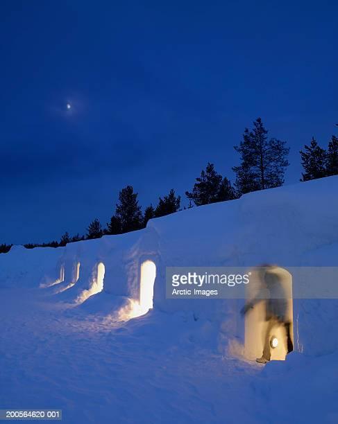 Finland, Lapland, Kakslauttanen, woman exiting igloo
