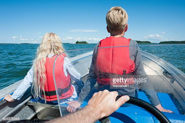 Finland, Turku archipelago, Houtskaer, father and his two children driving in motorboat