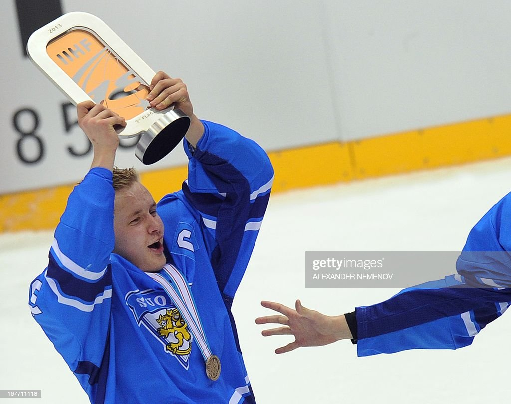 Finland's captain Alexi Mustonen celebrates with a trophy after his team defeated Russia in a IIHF U18 International Ice Hockey World Championship bronze medal match in Sochi on April 28, 2013.