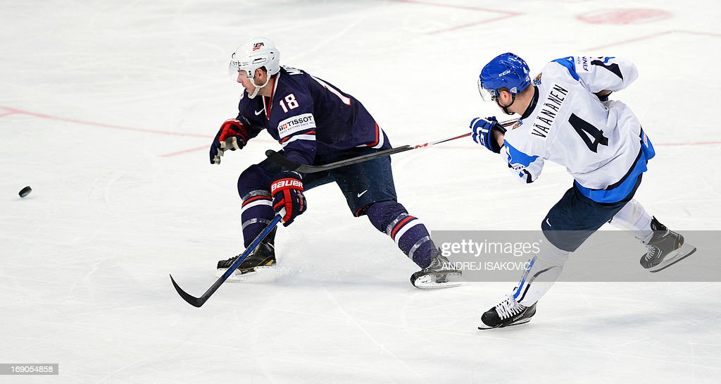 Finland's defender Ossi Vaananen (R) shoots the puck past US forward David Moss during the third place match Finland vs United States of the IIHF International Ice Hockey World Championship at Globe Arena in Stockholm on May 19, 2013.