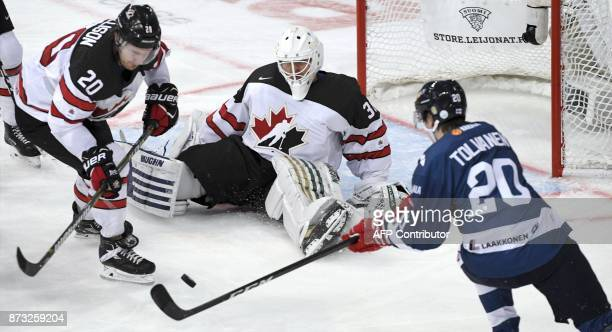 Finland's Eeli Tolvanen Canada's Matti Ellison and Canada's goalie Ben Scrivens vie for the puck during the Ice Hockey Euro Hockey Tour Karjala Cup...