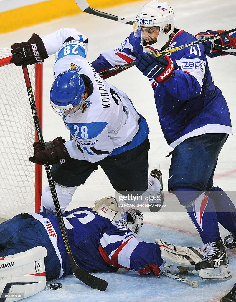 Finland's forward Lauri Korpikoski (L) attacks French goalie Fabrice Lhenry as French forward Pierre-Edouard Bellemare (R) stops him during a preliminary round game Finland vs France of the IIHF International Ice Hockey World Championship in Helsinki on May 6, 2013. AFP PHOTO/ ALEXANDER NEMENOV +++RESTRICTED TO EDITORIAL USE+++