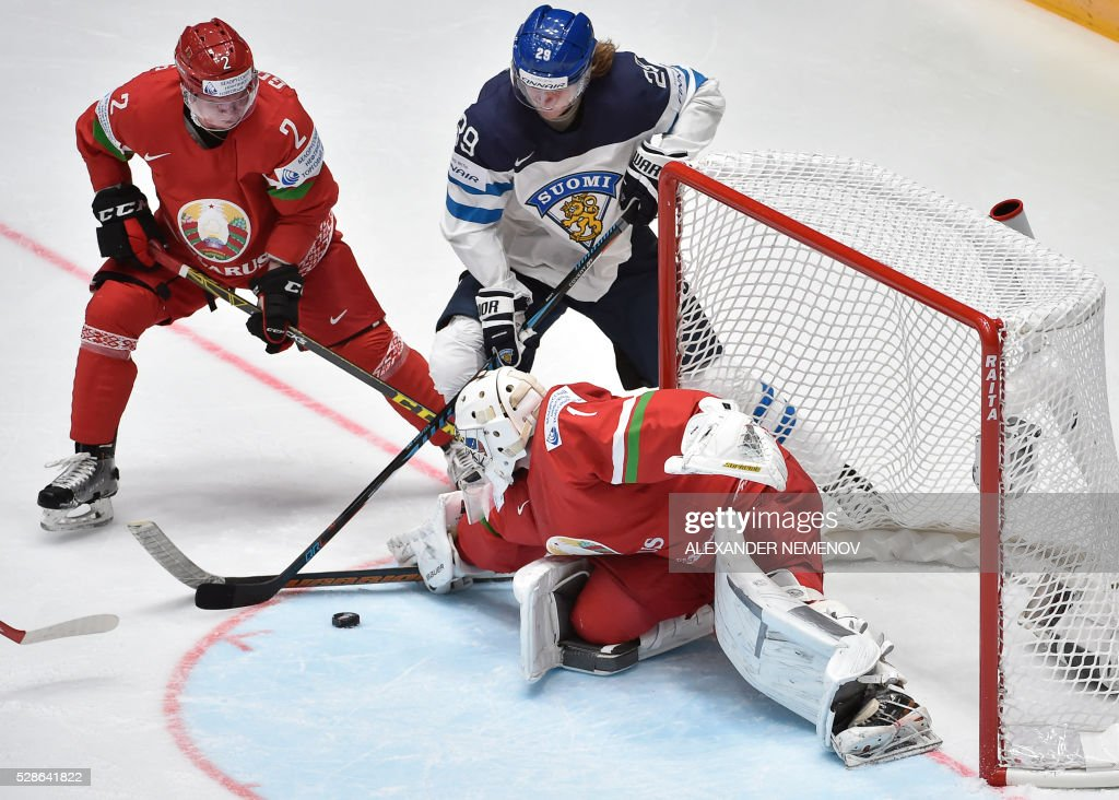 Finland's forward Patrik Laine (C) attacks Belarus' goalie Vitali Koval (C), as Belarus' defender Kirill Gotovets (L)stops him during the group B preliminary round game Finland vs Belarus at the 2016 IIHF Ice Hockey World Championship in St. Petersburg on May 6, 2016. / AFP / ALEXANDER