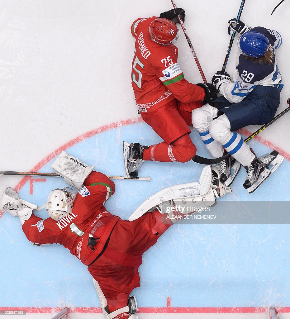Finland's forward Patrik Laine (R) vies with Belarus' defender Oleg Yevenko (C) in front of the net of Belarus' goalie Vitali Koval during the group B preliminary round game Finland vs Belarus at the 2016 IIHF Ice Hockey World Championship in St. Petersburg on May 6, 2016. / AFP / ALEXANDER