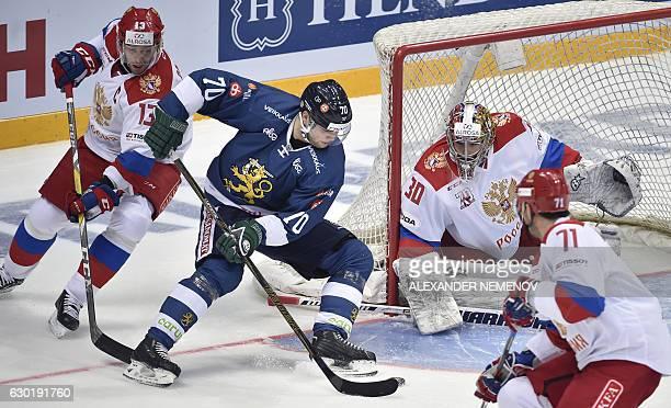 Finland's forward Teemu Hartikainen attacks the net of Russia's goalkeepr Igor Shestyorkin as Russia's forwards Pavel Datsyuk and Ilya Kovalchuk try...