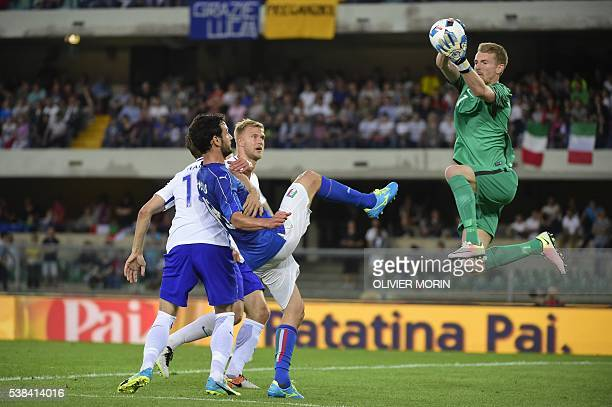 Finland's goalkeeper Lukas Hradecky makes a save in front of Italy's Marco Parolo during the friendly football match Italy vs Finland on June 6 in...