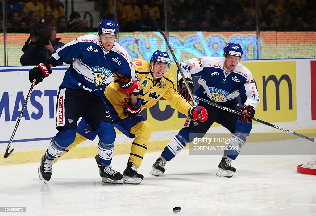 Finland's Ilari Melart and Mikko Kalteva vie with a Swedeish player during Euro Hockey Tour game between Sweden and Finland in Stockholm Hovet Aren...