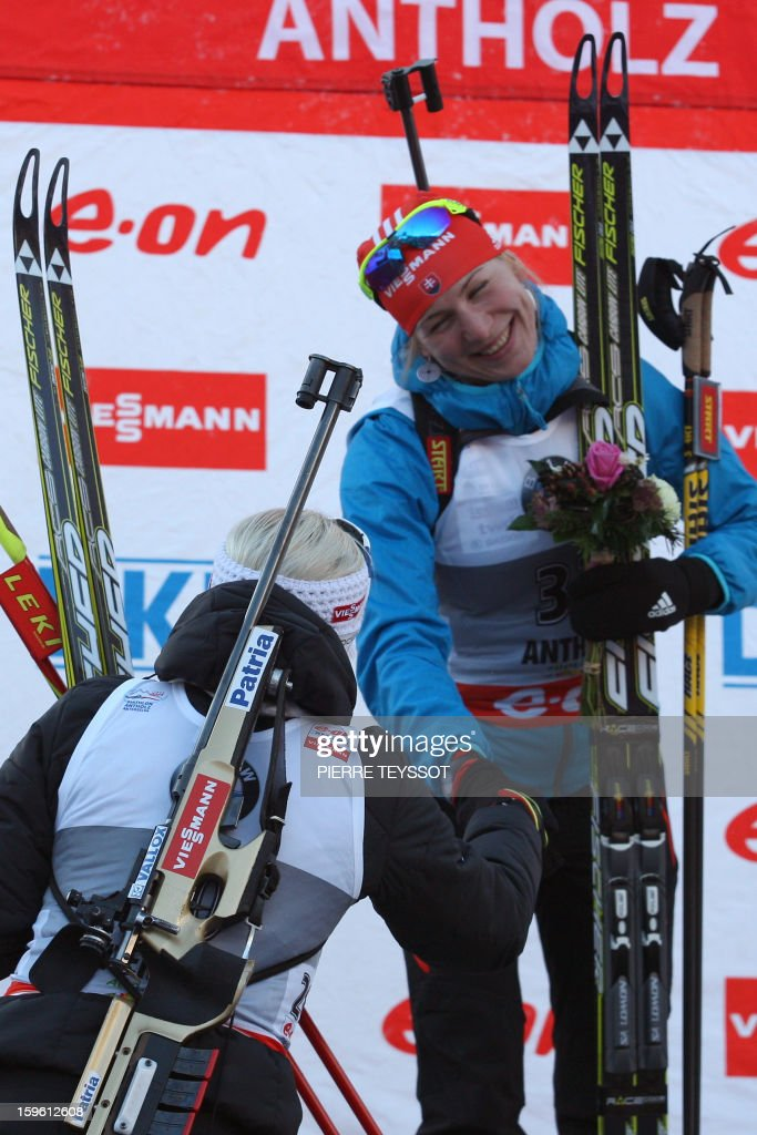 Finland's Kaisa Makarainen congratulates Slovakia's Anastasiya Kuzmina on the podium of the sprint race of the Women's biathlon World Cup on January 17, 2013 in Anterselva - Antholz. Kuzmina won the event.