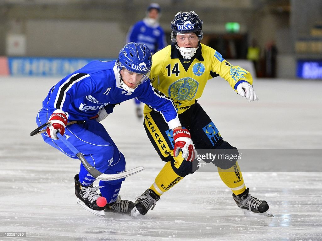 Finland's Markus Kumpuoja (L) and Kazakhstan's Andrey Morokov vie for the ball during the bronze medal match Finland vs Kazakhstan at the Bandy World Championship in Vanersborg, Sweden on February 3, 2013.