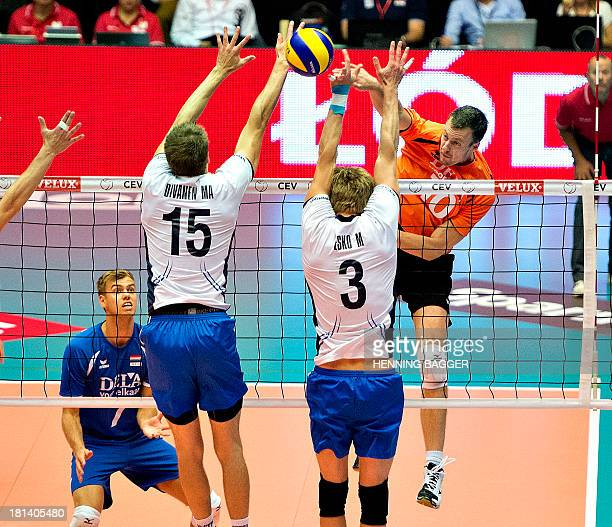 Finland's Matti Oivanen and Mikko Esko try to block a ball played by Dutch Jeroen Rauwerdink during the Velux 2013 European Championship Men Group C...