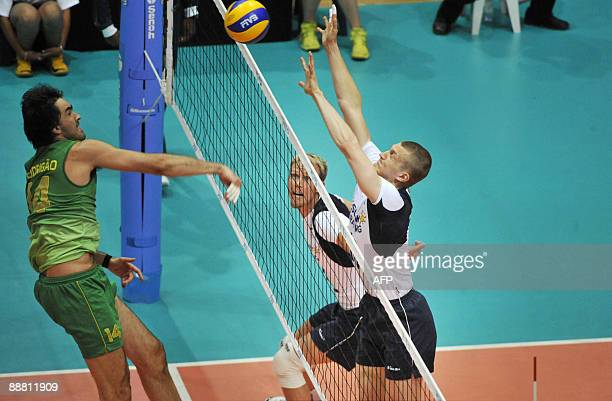 Finland's Mikko Esko watches as Jukka Lehtonen jumps to block Brazil's Rodrigo Santana's spike during the FIVB World League volleyball match between...