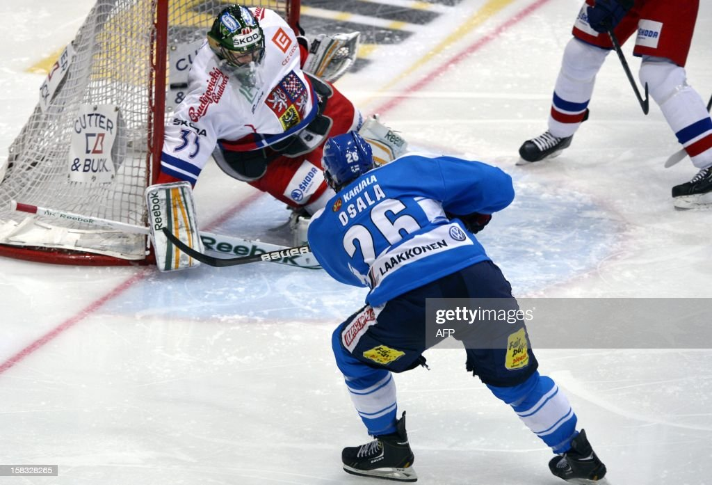Finland's Oskari Osala scores the equalizing 1-1 goal past Czech goalie Alexander Salak (L) during the second period of the Ice hockey Euro Hockey Tour's Channel One Cup match Finland vs Czech Republic in Helsinki on December 13, 2012.