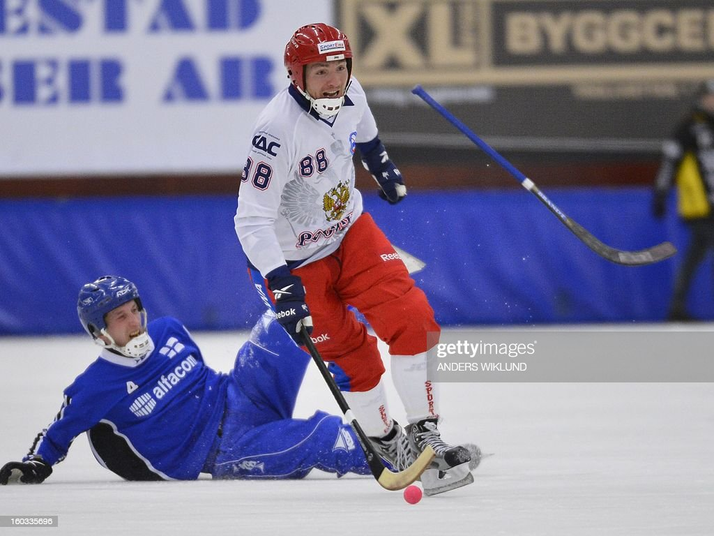 Finland's Pekka Hiitunen (L) falls and Russia's Evgeny Ivanushkin vie for the puck during the Bandy World Championship match between Finland and Russia in Trollhattan, Sweden, on January 29, 2013.