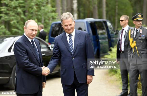 Finland's President Sauli Niinisto welcomes Russian President Vladimir Putin during their meeting in Punkaharju hotel in Savonlinna Finland on July...