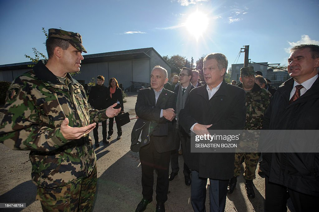 Finland's President Sauli Niinistoe (3R) amd Swiss President Ueli Maurer (2L) speak with a military during a visit to rescue troops at a Swiss military base on October 16, 2013 in Bremgarten.