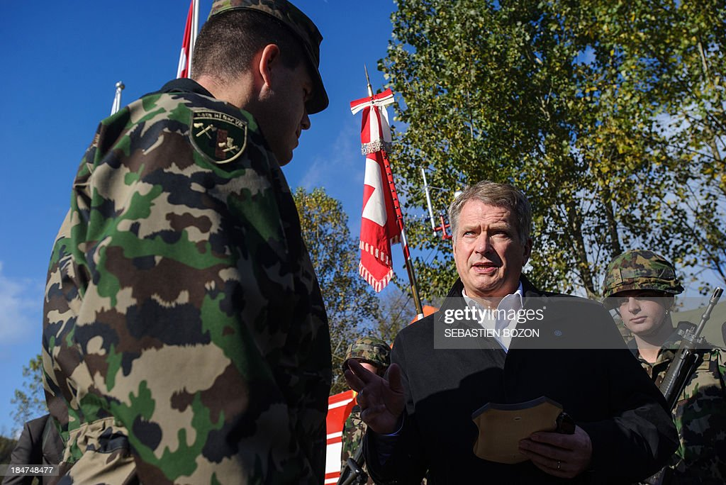 Finland's President Sauli Niinistoe (R), speaks with a military during a visit to rescue troops at a Swiss military base on October 16, 2013 in Bremgarten. AFP PHOTO / SEBASTIEN BOZON