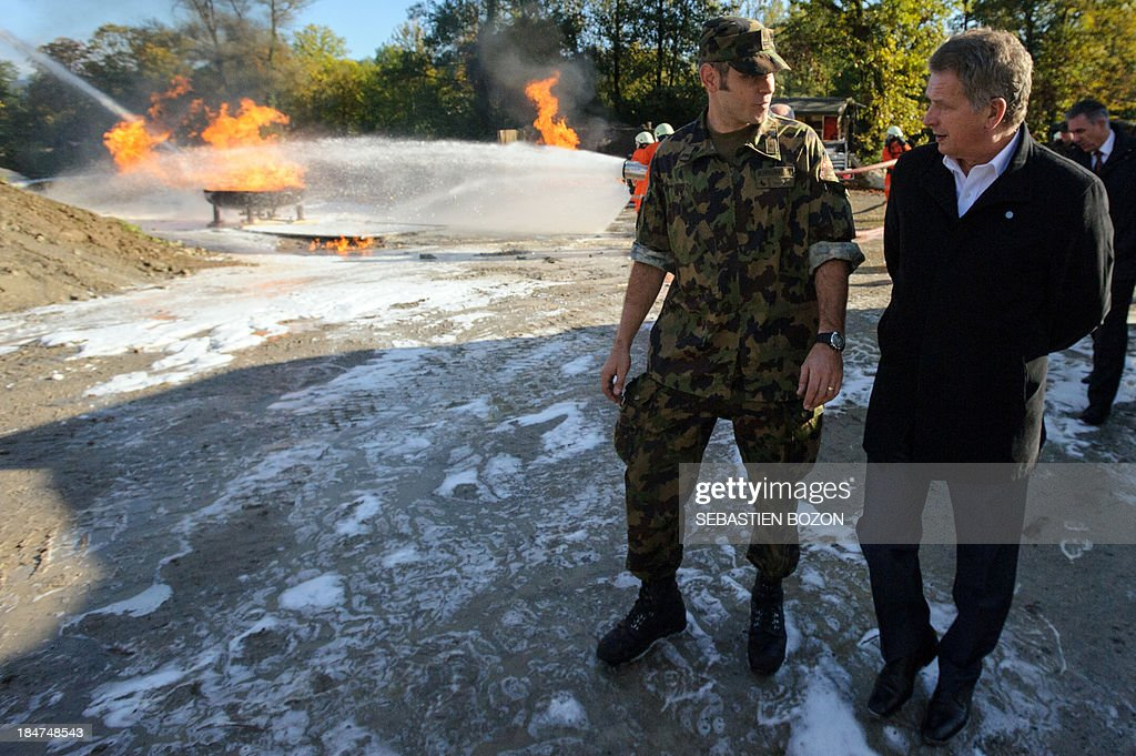 Finland's President Sauli Niinistoe (R) speaks with a military during a visit to rescue troops at a Swiss military base on October 16, 2013 in Bremgarten.