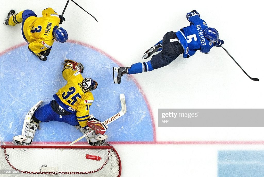 Finland's Rasmus Ristolainen (R) flicks the winning goal into the net behind Sweden's goalie Oscar Dansk during the World Junior Hockey Championships final match between Sweden and Finland at Malmo Arena in Malmo, on January 5, 2014.