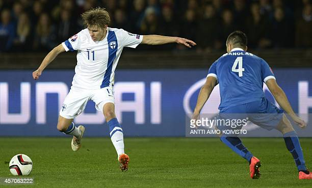 Finland's Riku Riski and Greece's defender Konstantinos Manolas vie for the ball during the Euro 2016 Group F qualifying football match Finland vs...