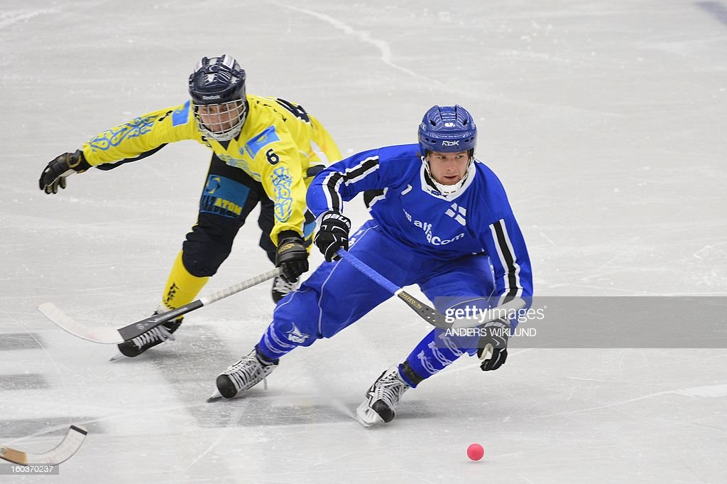Finland's Rolf Larsson (R) and Kazakhstan's Sergey Gorchakov vie for the ball during the Bandy World Championship match Finland vs Kazakhstan in Vanersborg, Sweden on January 30, 2013.