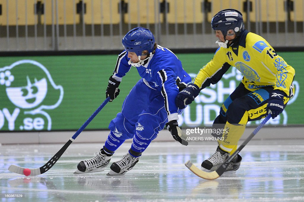 Finland's Rolf Larsson (L) and Kazakhstan's Yuriy Loginov (R) vie for the ball during the Bandy World Championship match Finland vs Kazakhstan in Vanersborg January 30, 2013.
