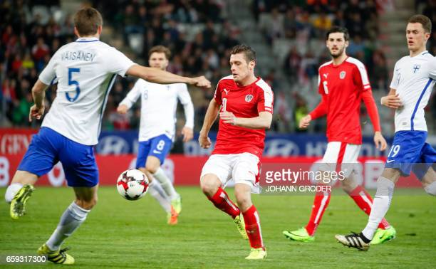 Finland's Sauli Vaeisaenen and Austria'S Zlatko Junuzovic vie for the ball during the friendly football match between Austria and Finland in...
