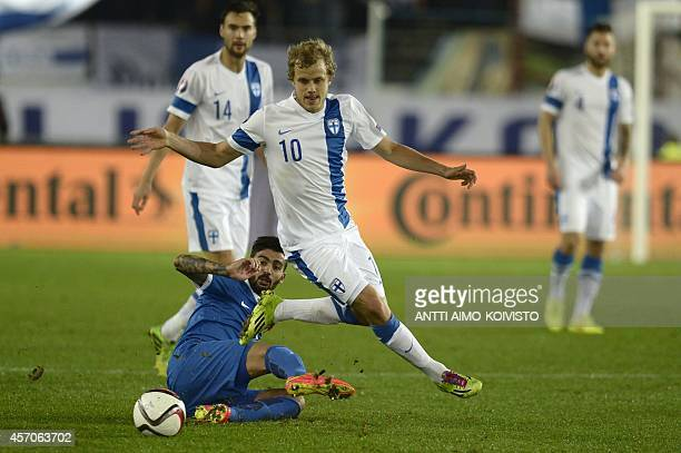 Finland's Teemu Pukki and Greece's defender Loukas Vyntras vie for the ball during the Euro 2016 Group F qualifying football match Finland vs Greece...