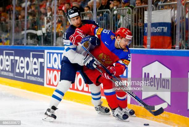 Finland's Valtteri Filppula and Russia's Bogdan Kiselevich vie during the IIHF Men's World Championship Ice Hockey bronze medal match between Russia...