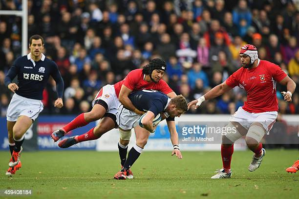 Finn Russell of Scotland is tackled by Latiume Fosita of Tonga during the autumn test international match at Rugby Park on November 22 2014 in...