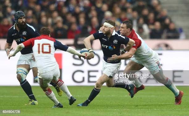 Finn Russell of Scotland offloads to teammate Josh Strauss of Scotland as he is tackled by Louis Picamoles of France during the RBS Six Nations match...