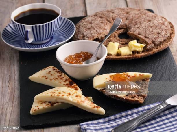 Finnish breakfast with traditional round bread reikäleipä, butter, cloudberry jam, Finnish squeaky cheese Leipäjuusto and black coffee