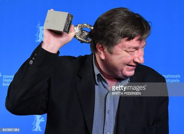 Finnish director and screenwriter Aki Kaurismaki poses with his Silver Bear for Best Director prize for his movie 'The Other Side of Hope' after the...