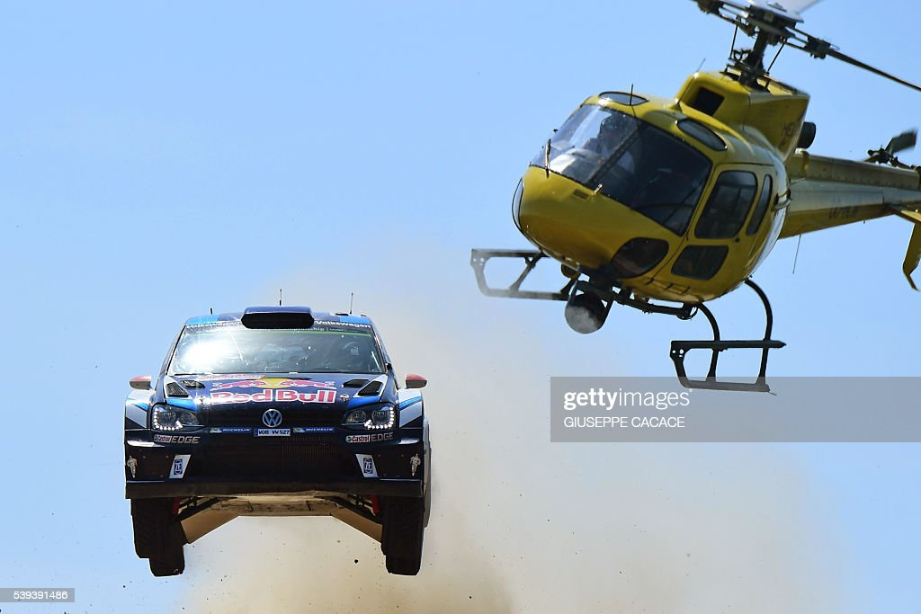 Finnish driver Jari Matti Latvala and Finish co-driver Miikka Anttila jump next to helicopter as the drive their Volkswagen Polo R WRC near Pattada, on the third day of the 2016 FIA World Rally Championship in Sardegna, on June 11 2016. / AFP / GIUSEPPE