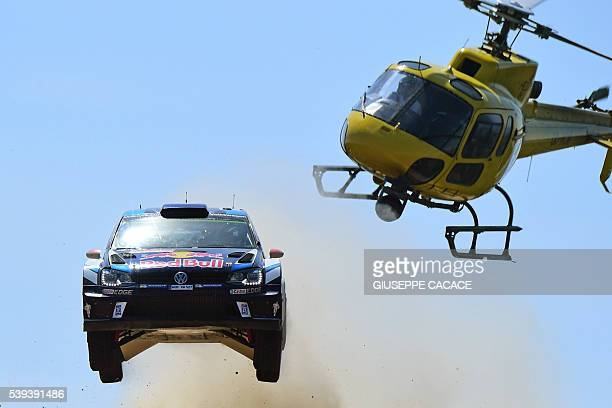 Finnish driver Jari Matti Latvala and Finish codriver Miikka Anttila jump next to helicopter as the drive their Volkswagen Polo R WRC near Pattada on...