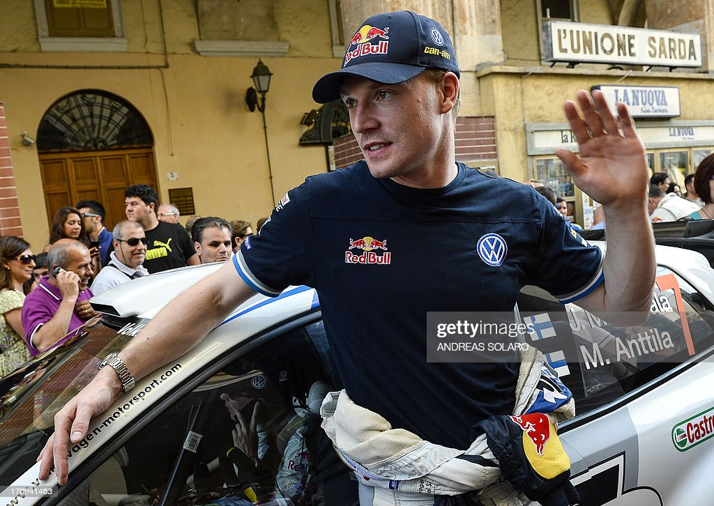 Finnish driver Jari Matti Latvala waves as he leans on his Volkswagen Polo R WRC during the opening ceremony of the FIA World Rally Championship of Italy in Sassari, on the Italian island of Sardinia on June 20, 2013.
