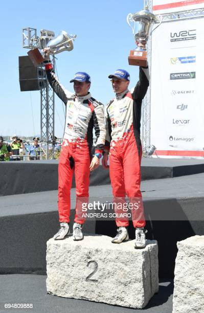 Finnish driver JariMatti Latvala and Finish codriver Miikka Anttila of Toyota Yaris WRC hold their trophies as they celebrate their second place on...