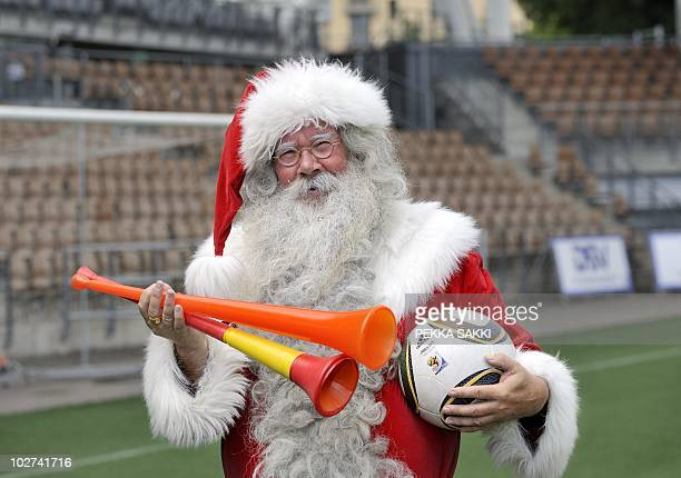 Finnish Father Christmas or Santa Claus holds out two vuvuzelas representing the Netherlands and Spain and the official World Cup ball Jabulani at...