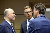 Finnish Finance Minister Alexander Stubb and European Union Commissioner for Economic and Financial Affairs Pierre Moscovici listen to Eurogroup...