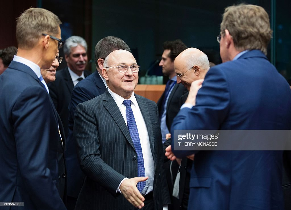 Finnish Finance Minister Alexander Stubb (L) and the Belgian Finance Minister Johan Van Overtveldt (R) talk with French Finance and Public Accounts Minister Michel Sapin (C) prior to a meeting of Eurogroup ministers at the European Council headquarters in Brussels on February 11, 2016. / AFP / THIERRY MONASSE